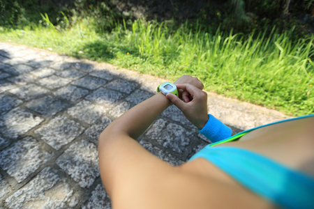 pulse trace: young woman jogger ready to run set and looking at sports smart watch, checking performance or heart rate pulse trace. Sport and fitness outdoors on forest trail.