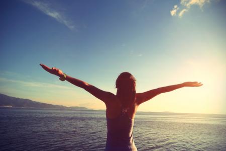 stretching: Mujer joven que anima basculador los brazos abiertos en la salida del sol junto al mar, efecto de la vendimia Foto de archivo