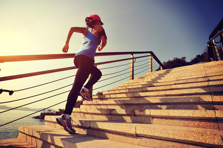 lifestyle outdoors: healthy lifestyle sports woman running up on stone stairs sunrise seaside