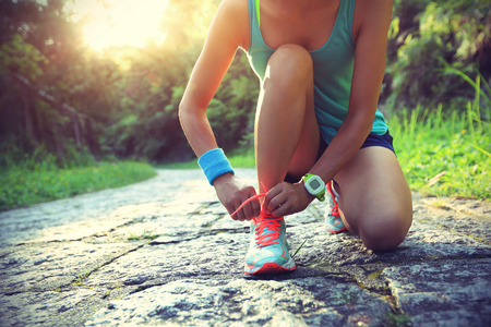sun energy: young woman runner tying shoelaces on stone trail Stock Photo