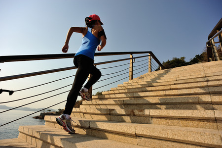 healthy lifestyle: healthy lifestyle sports woman running up on stone stairs sunrise seaside