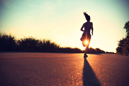 human energy: young fitness woman running on sunrise seaside trail