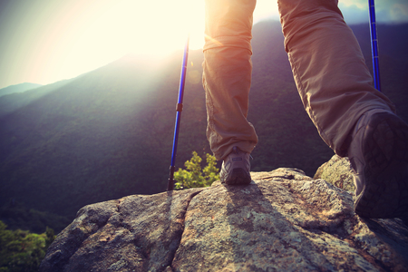 hiking boots: young woman hiker legs on sunrise mountain peak rock Stock Photo