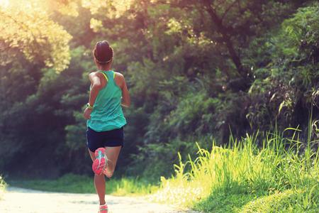 corriendo: Runner atleta corriendo en pista forestal. mujer de fitness trotar entrenamiento concepto de bienestar. Foto de archivo