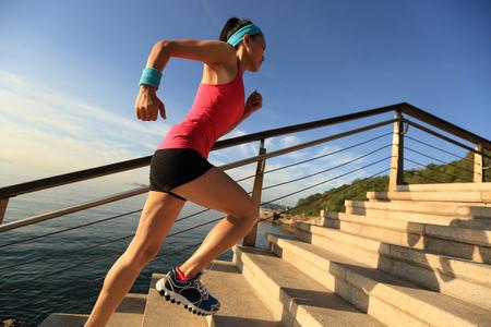 escalera: Corredor de la mujer de la aptitud que se ejecuta en las escaleras junto al mar Foto de archivo