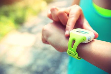 mujer joven basculador listo para correr ajustado y mirando a los deportes reloj inteligente, comprobar el funcionamiento o el pulso del ritmo cardíaco rastro. El deporte y la aptitud al aire libre en pista forestal.