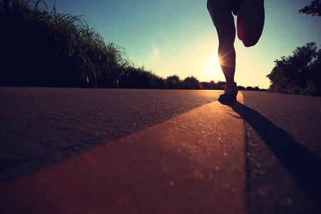 gente corriendo: jóvenes piernas de la mujer de la aptitud que se ejecutan en la salida del sol sendero costero Foto de archivo