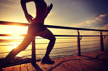 sports and fitness: young fitness woman legs running on sunrise seaside trail Stock Photo