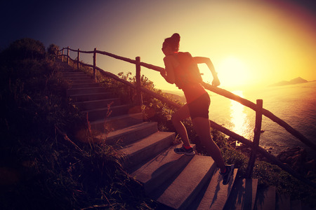 escalera: fitness mujer trail running en las escaleras de la montaña junto al mar, la capacitación de campo través. Foto de archivo