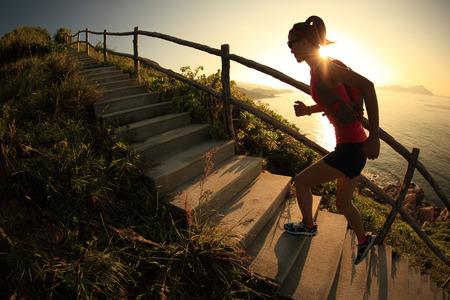 escalera: fitness mujer corredor de carreras de montaña en las escaleras de la montaña en el mar, la formación para funcionamiento a campo través.