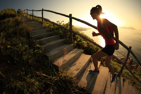 mountains and sky: fitness woman trail runner running on seaside mountain stairs, training for cross country running.