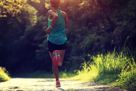 coureur: Runner athlète qui court sur le sentier de la forêt. femme de remise en forme du jogging entraînement concept de bien-être.