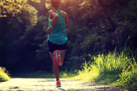 personas trotando: Runner atleta corriendo en pista forestal. mujer de fitness trotar entrenamiento concepto de bienestar. Foto de archivo