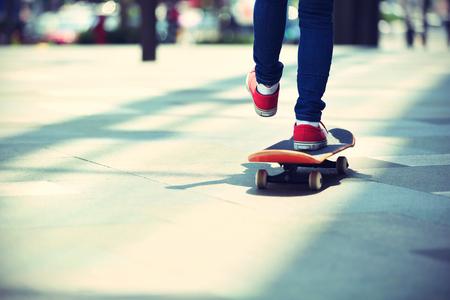 skateboard: young skateboarder legs riding on skateboard on city