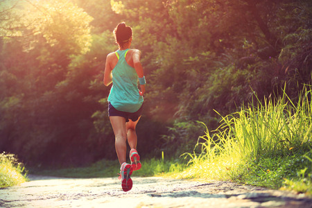pathway: Runner athlete running on forest trail. woman fitness jogging workout wellness concept.