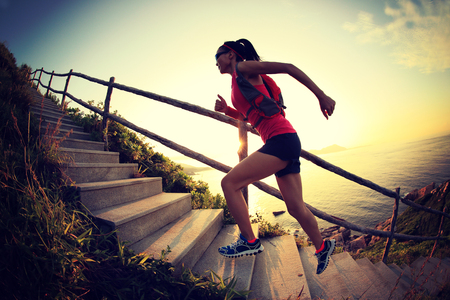 runners: fitness woman runner trail running on seaside mountain stairs, training for cross country running.