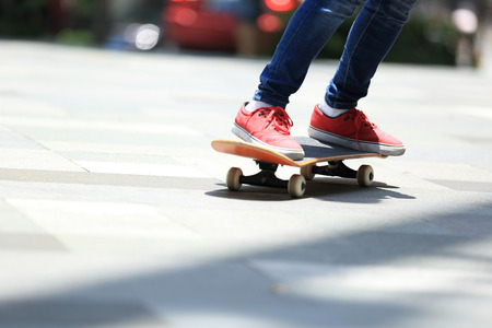 skateboard shoes: young skateboarder legs riding on skateboard on city