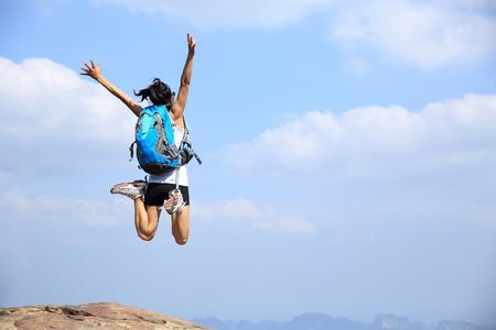 若いアジア女性山ピーク崖の上ジャンプ