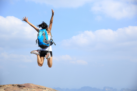 young asian woman jumping on mountain peak cliff Stock Photo