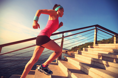 runners: healthy lifestyle sports woman running up on stone stairs seaside