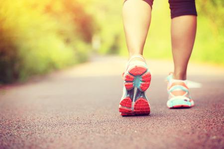 piernas jóvenes fitness mujer caminante en la pista forestal