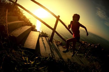 climbing stairs: fitness mujer trail running en las escaleras de la monta�a junto al mar, la capacitaci�n de campo trav�s. Foto de archivo