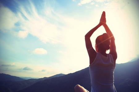 mani incrociate: giovane donna yoga sedersi meditazione sulla cima della montagna alba