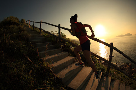 stone steps: fitness woman runner trail running on seaside mountain stairs, training for cross country running.