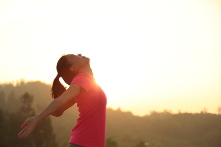 human arms: cheering young asian woman open arms at sunrise mountain peak Stock Photo