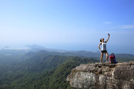 taking photo: woman hiker taking photo with smart phone at mountain peak