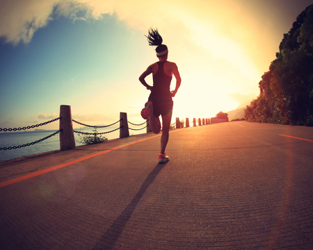 sports activities: young fitness woman running on sunrise seaside trail