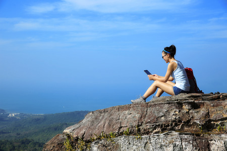 table mountain national park: woman hiker use digital tablet at mountain peak cliff