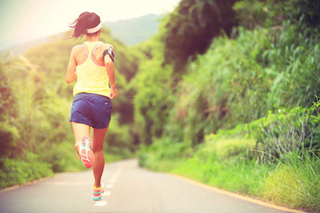 personas trotando: fitness mujer corredor de pista que se ejecuta en pista forestal, la formación para funcionamiento a campo través. Foto de archivo