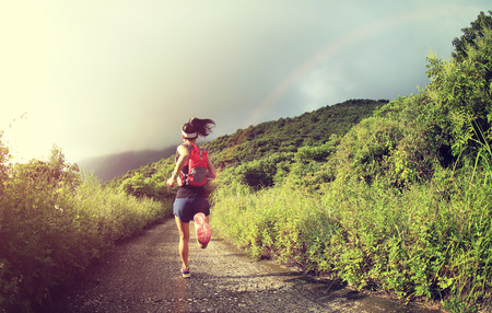 trails: young fitness woman trail runner running on seaside mountain