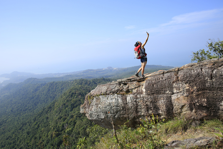 mountain top: young woman hiker taking photo with smart phone at mountain peak