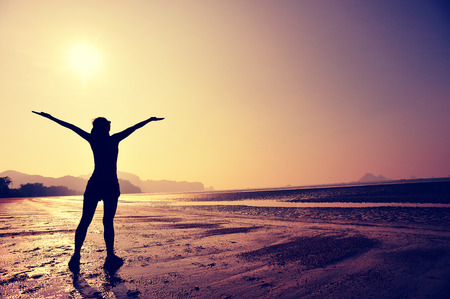 freedom woman: cheering young woman open arms on sunrise beach Stock Photo