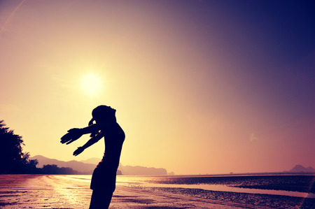 retro woman: cheering young woman open arms on sunrise beach Stock Photo