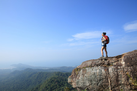 woman relax: woman hiker enjoy the view at sunset mountain peak cliff