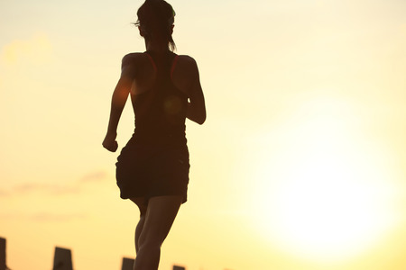 woman street: young fitness woman running on sunrise seaside trail