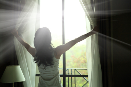 indoors: girl opening curtains in a bedroom
