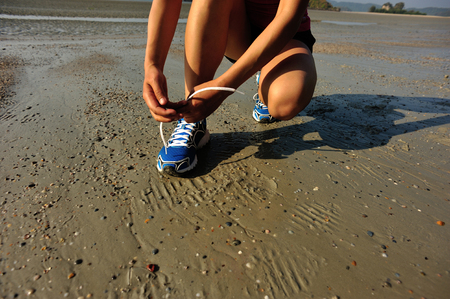 shoelace: woman runner tying shoelace before running on beach