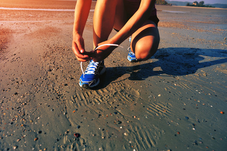 outdoor training: woman runner tying shoelace before running on beach