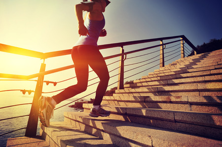 woman stairs: healthy lifestyle sports woman running up on stone stairs sunrise seaside