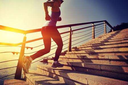 climbing stairs: mujer sana de los deportes de estilo de vida con procesamiento de escaleras de piedra junto al mar salida del sol Foto de archivo