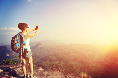 outdoor photo: young woman hiker taking photo with smart phone at mountain peak