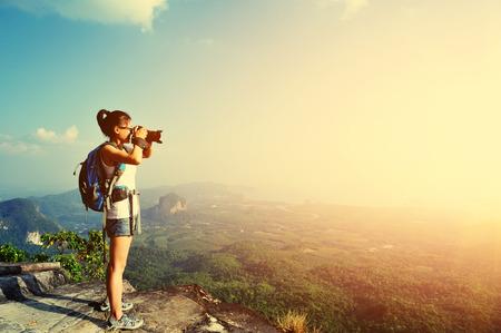 mochila de viaje: joven fotógrafo toma fotos en el pico de la montaña
