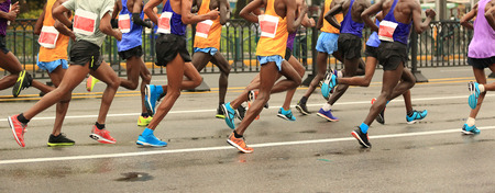 marathon runners running on city road Imagens