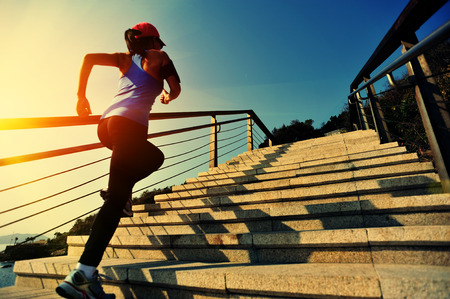 asian sport: healthy lifestyle sports woman running up on stone stairs sunrise seaside