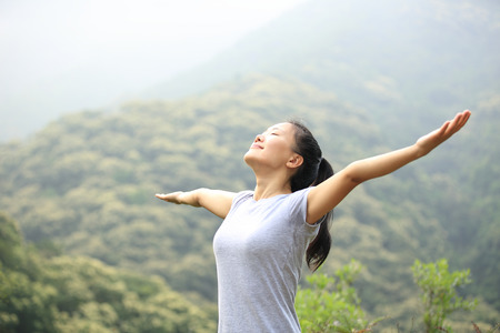 cheering woman enjoy the beautiful view at mountain peak