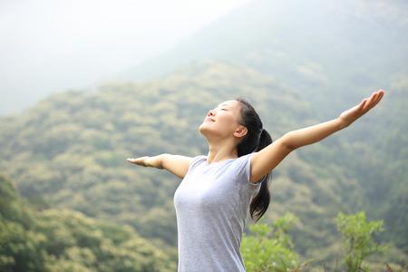 cielos abiertos: mujer animando disfrutar de la hermosa vista al pico de la montaña